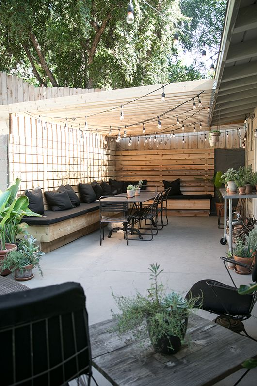 Cute backyard gathering area. Love the banquette style seating which looks wide enough for a nap. Must be so pretty at night wit the lights on