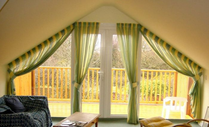 living room curtains ideas, sofa in dark colors and wooden table, terrace door decorated with two sets, of green and yellow striped curtains