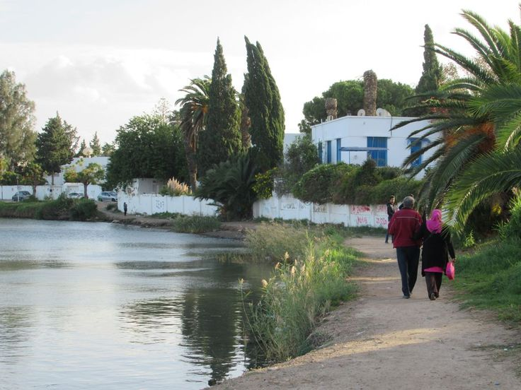A couple strolls along the bank of the ancient Punic port of Carthage near Tunis, Tunisia.