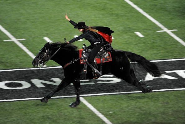 The Masked Rider crosses the field to open the game!
