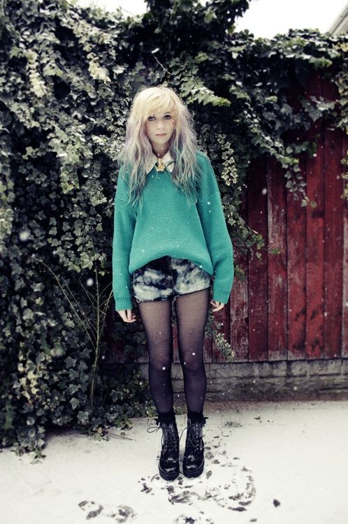 green knit with shirt underneath and shorts with black tights