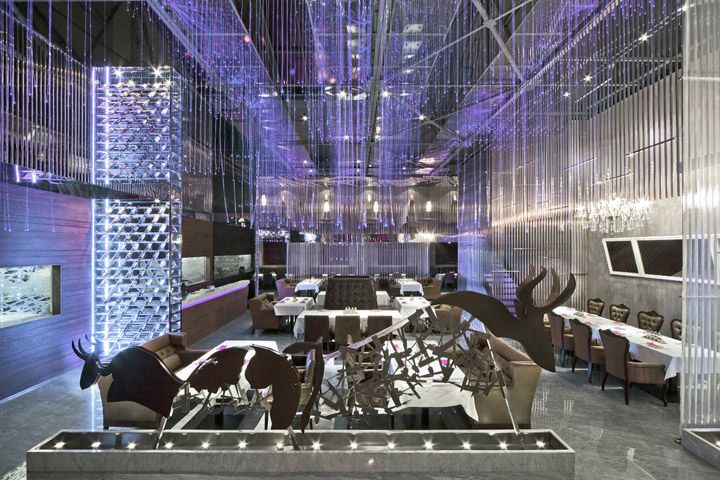 Starry Night Dining by Panorama International, WuXi   China 2m high bull-shaped partition made by knifes & forks gave clue and defined brand identity to the restaurant. Verticality & spaciousness of the atrium dining zone were emphasized through full-height mirror stainless steel wine rack and crystal chandelier above the VIP table. Ceiling suspended fibre optics in violet colour created starry night effect to the leather-upholstered central & periphery booth seating areas.