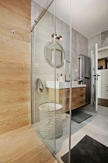 Teplý drevený dekor na obklade a dlažbe v sprchovacom kúte a na zástene toalety podporil obklad z gresu a dlažba s betónovým dekorom.