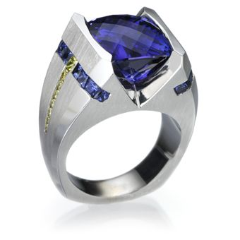 18k white gold gents ring featuring a 11.84ct tanzanite, 1.70ctw blue sapphires and 0.43ctw yellow diamonds.