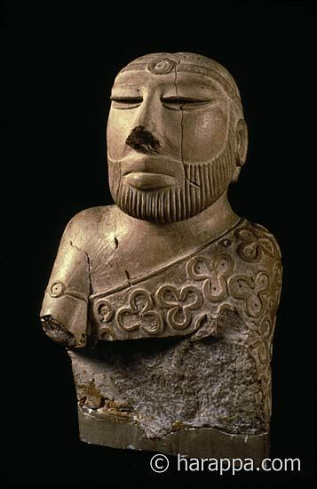 """Priest King"" from Mohenjo-daro. Fillet or ribbon headband with circular inlay ornament on the forehead and similar but smaller ornament on the right upper arm. The two ends of the fillet fall along the back and though the hair is carefully combed towards the back of the head, no bun is present. The flat back of the head may have held a separately carved bun as is traditional on the other seated figures, or it could have held a more elaborate horn and plumed headdress."