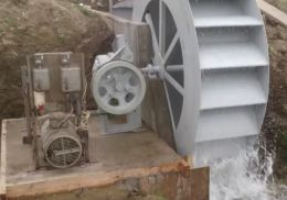 Water Wheel Generator - Homemade water wheel generator constructed from steel stock, bearings, a PTO assembly, and a generator.