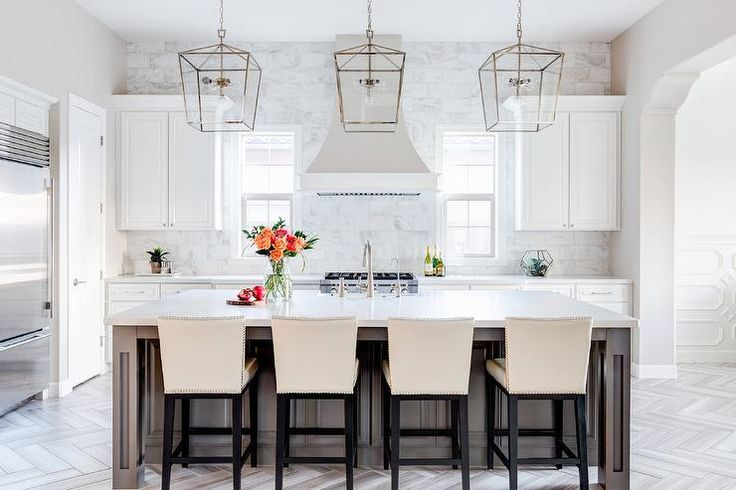 Stunning transitional kitchen boasts a gray center island seating cream leather counter stools and topped with white quartz countertops lit by three Darlana 4 Light Lanterns in brass.