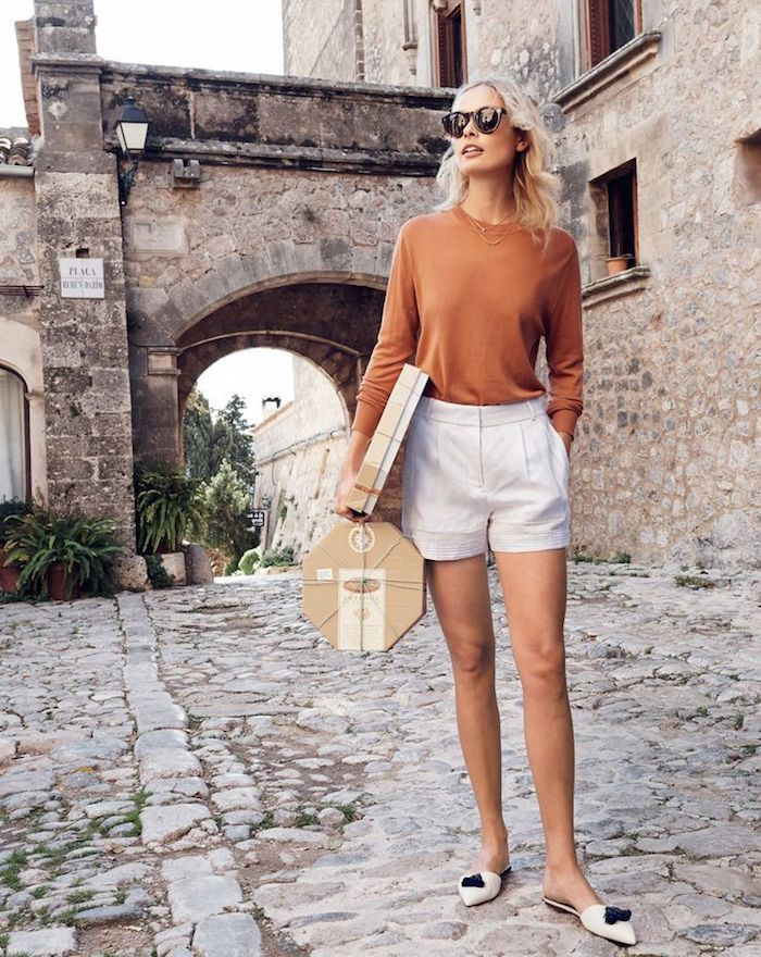 high waisted natural white linen shorts, pumpkin orange crew neck sweater, white mules with black accents with paper luggage