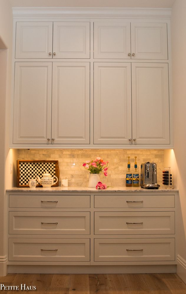 Coffee bar with farmhouse white kitchen cabinets and marble counters