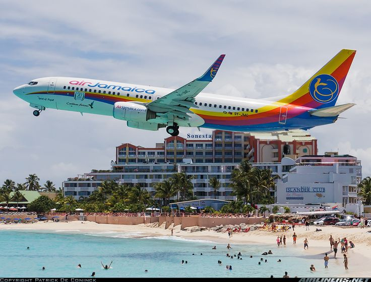 A colorful Air Jamaica 738 departing from St. Maarten, flying above the crowded, world-famous Maho Beach.