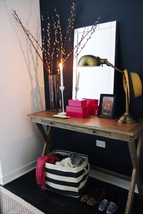 Chic styled foyer with navy blue paint color accent wall, World Market Campaign Console Table, West Elm Mirror-Framed Wall Mirror, The Container Store Rugby Stripe Bin, Ikea Blomster Candle Holders, hot pink lacquer boxes and brass lamp.