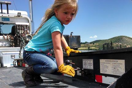 """Adelyn of Colorado Grandpa Carl wrote, """"This photo is of my 4 year old granddaughter taken by my son in law; He moves heavy equipment with a semi tractor trailer lowboy. She rode with him and was helping unload by operating the hydraulic levers, the picture is completely unstaged. My first thought was """"Kinco gloves… Made for the next generation of the American work force!"""" What better face than a 4 year old girl operating a semi tractor trailer lowboy."""""""