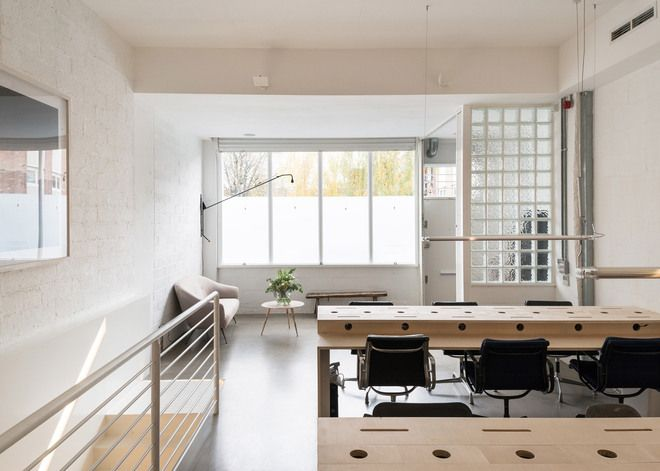Charming A Bright And Open Office With Plywood Furniture, Black Chairs, Painted Concrete  Block Walls