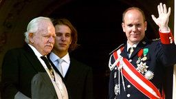 Fürst Rainier von Monaco, sein Enkelsohn Andrea Casiraghi und Prinz Albert (l) winken.