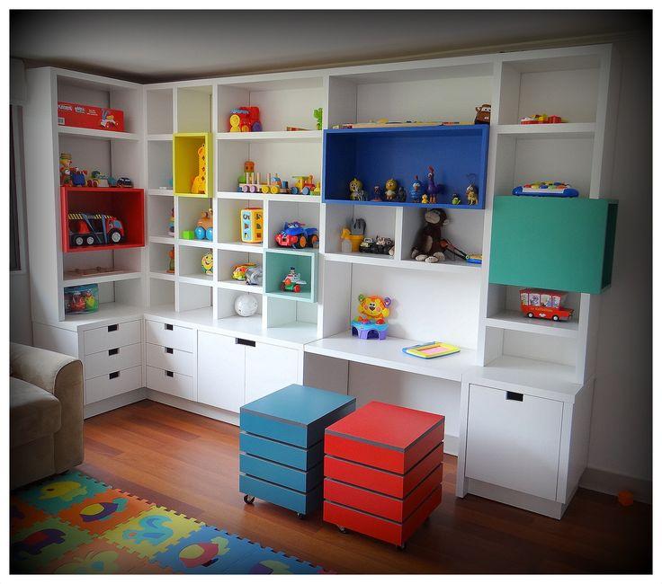 Mueble biblioteca enchapado blanco, con aplicaciones de cajones en colores fuertes. Sistemas de cajones profundos para guardado de juguetes y cajones basicos. Sin tirador, con cortes rectangulares como manilla. Dos cajas en treillage para guardado de objetos. Rieles telescopicos, enchape lamitech.