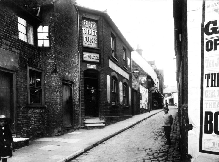 """The Three Tuns in Tunsgate, Guildford.  Closed c.1930.  """"W. Boozer"""" over the door is the licensee's name."""