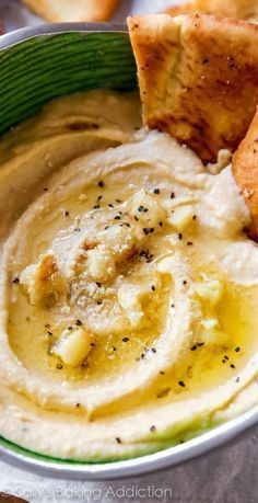 This roasted garlic hummus is addictive. The whole bowl will be gone in 5 minutes. Plus, a recipe for homemade crunchy pita chips! @sallybakeblog