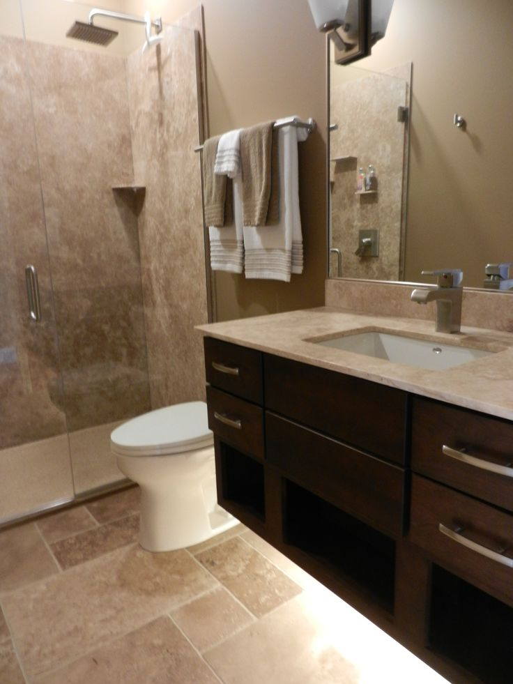 Floating vanity with under cabinet lighting for a modern bathroom.