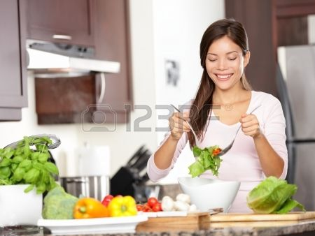Woman making salad in kitchen  Healthy eating lifestyle concept with beautiful young woman cooking in her kitchen  photo