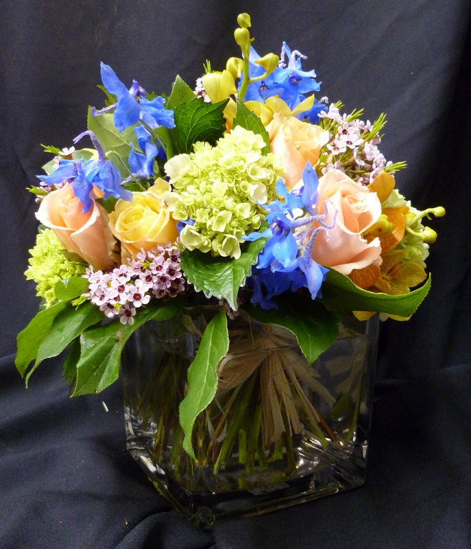This is a cube vase floral arrangement that features roses for Pink and blue flower arrangements