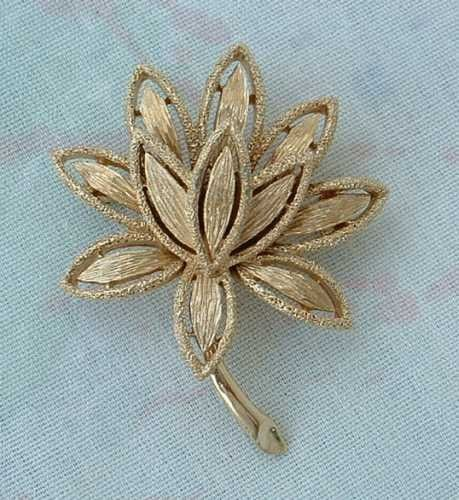 """This lovely pin has a man-petaled floral arrangement with richly textured petals. The pin measures 2"""" x 1-5/8"""" and is in excellent condition. The back is marked """"AVON ©."""" The pin will be shipped in a"""