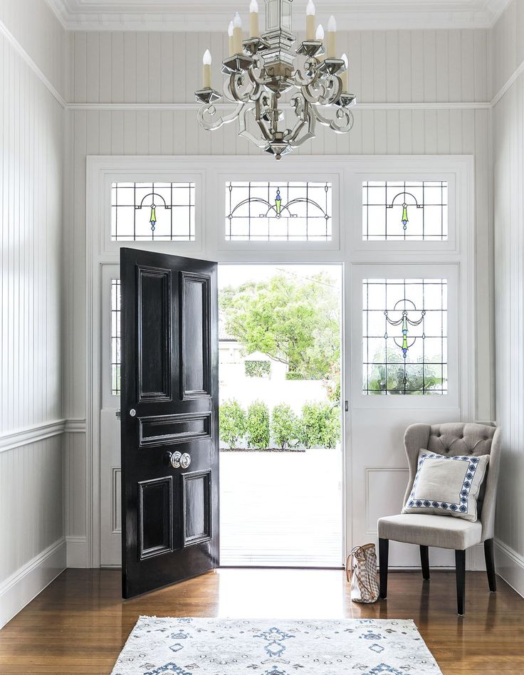 Entryway: black front door, stained glass windows, pale grey vertical wooden wall panelling, chandelier, high ceiling, timber floorboards