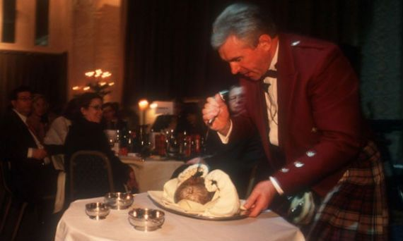 A man in Highland dress cuts the haggis during a Burns' Night celebration at Stirling Castle