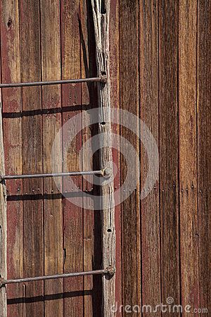 An old wooden ladder on the side of an abandoned building