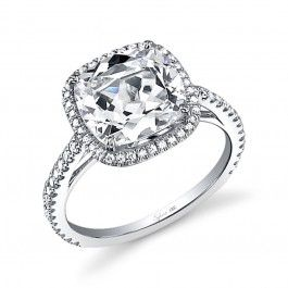 This magnificent white gold engagement ring features a unique and dazzling 1.5 carat cushion cut diamond center accentuated by a shimmering halo of round brilliant diamonds. Cascading diamonds down the shank create a flow of breathtaking sparkle as it holds the glorious crown. The total weight of this stunning setting is 0.43 carats.