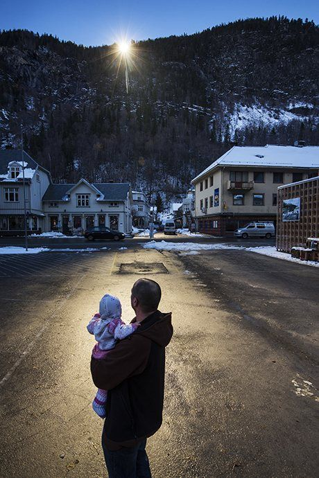 A man holds his baby up to the light reflected by the mirrors. Photograph: David Levene for the Guardian