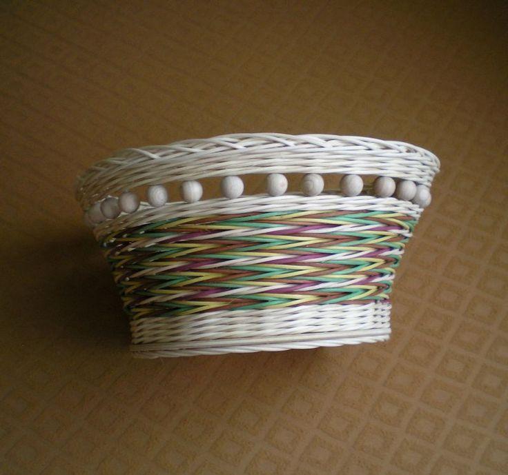 Kulatý košíček Košíček pletený z přírodního a barevného pedigu s pevným překližkovým dnem, zdobený dřevěnými korálky. Průměr dna 20 cm, horní průměr 28 cm. Výška 14 cm.
