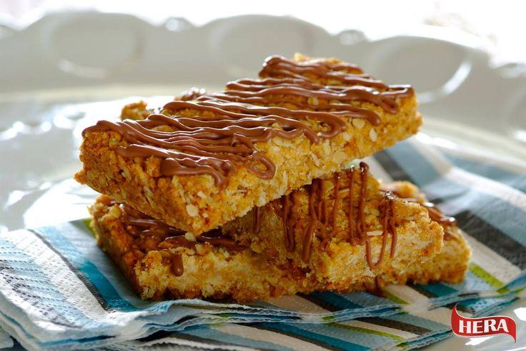 Ingredience: - 1 ¼ šálku polohrubé mouky - 1 ¼ šálku ovesných vloček - 1 ¼ šálku kokosu - ¾ šálku cukru - 5 čajových lžiček sirupu - 125g Hery máslové (půl balení) - 1 čajová lžička jedlé sody - 3-4 polévkové lžíce vroucí vody - 4 kostičky čokolády, rozpuštěné Jako první smíchejte suché přísady. Následně rozpusťte sirup s Herou máslovou. Smíchejte sodu s vroucí vodou a přidejte k rozpuštěné Heře máslové, vše pak smíchejte se suchými přísadami. Směs natlačte do pekáče a pečte 20 minut.
