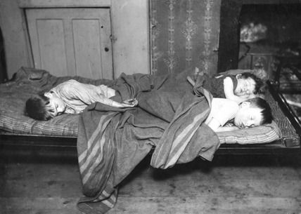 Slum children in bed, Bethnal Green, 1900-1910.