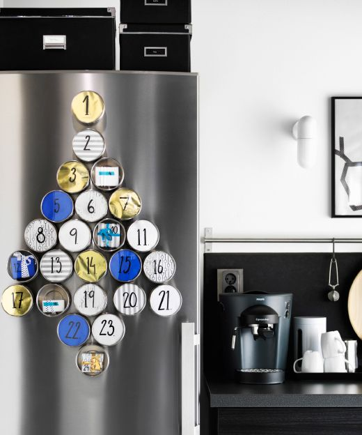 A stainless steel fridge decorated with magentic containers filled with paper and numbered and arranged in the shape of a Christmas tree.