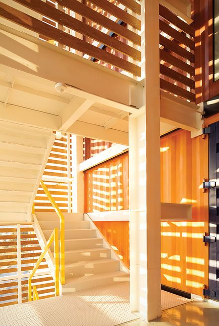 This bright exterior stairwell is wrapped in wood. Courtesy of: Jaime Sicila