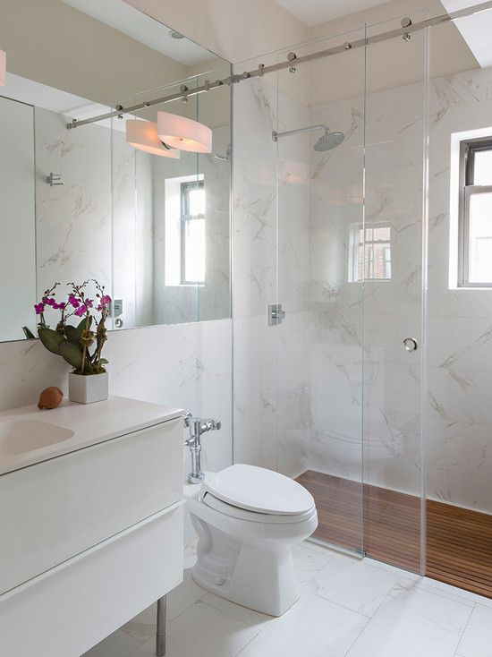 Banheiro branco com piso do box em deck de madeira