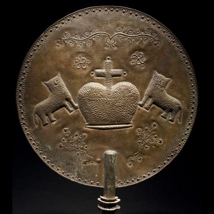Culture Ashanti, Ghana. Bronze et os. H. 61cm - D. 36cm Eventail utilisé comme objet d'apparat. Superbe travail mêlant les techniques du métal repoussé et de la fonte à la cire perdu. Objet datant de la période colonial, comme l'atteste le motif central, représentant la couronne de saint Édouard, symbole de la monarchie britannique. Cette indication permet de dater cet objet d'avant 1957, date de l'indépendance du Ghana.
