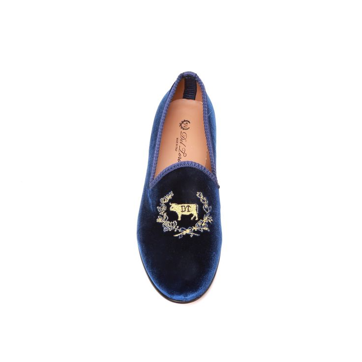 Men's Navy Velvet Slipper with Gold Del Toro Logo Embroidery and Navy Grosgrain Trim. Signature Red Grosgrain Heel Stripe. Leather Sole and Lining. Brown Stacked Wooden Heel. Handmade in Italy.