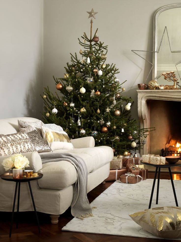 A sumptuous sofa in a neutral shade offsets sparkling decorations on the Christmas tree and fireplace. Contrast textures by combining wool and linen with reflective satin smooth surfaces.