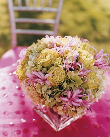 Nerines, hydrangea, and roses mingle in a centerpiece atop a sequined fuchsia tablecloth.