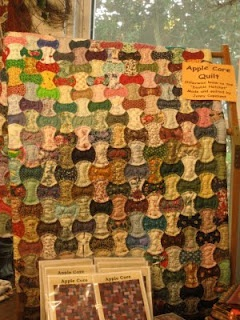 Small apple core quilt on display at the counter of a quilt shop (with pattern in front)