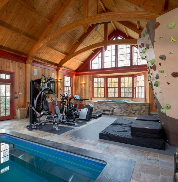 """This inspiration is defiantly for the avid climber amongst you. Griffiths Construction have converted this beautiful barn by installing a climbing wall, an area for weights and cardio machines. There is a swimming pool at the fore-front and then to the rear of the barn you will see a jacuzzi raised and set within the bay window. The polished wooden walls and ceiling are magnificent."""