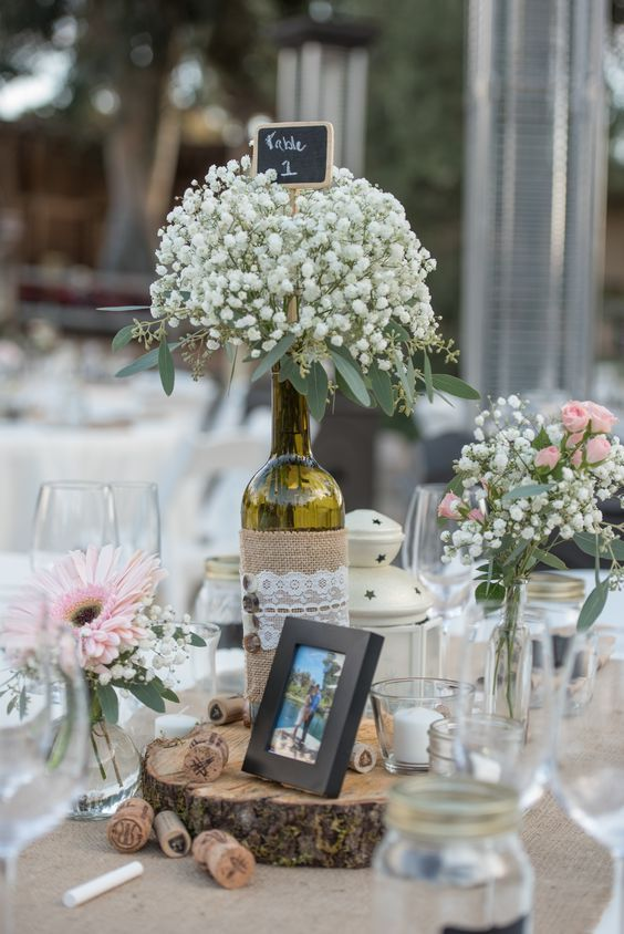 Wine Bottle Centerpieces with Baby's Breath / http://www.deerpearlflowers.com/wine-bottle-vineyard-wedding-decor-ideas/