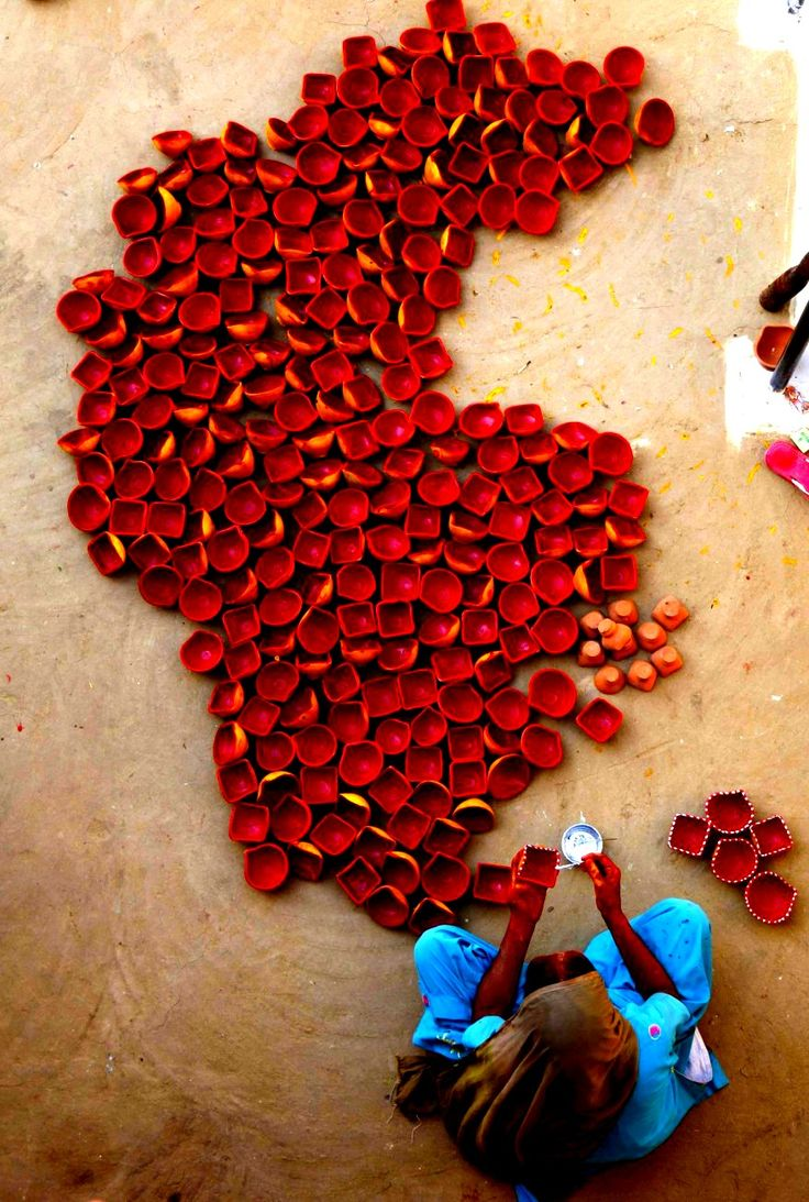 An Indian woman paints earthen lamps on the outskirts of Jammu ahead of Hindu festival Diwali. Diwali, the festival of lights - India