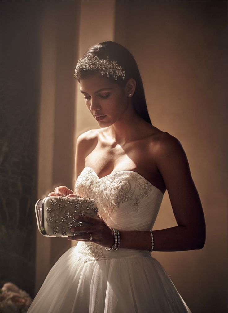A sparkling bridal headpiece, crystal minaudiere, and delicate jewels make for a beautifully accessorized wedding day look. Book your appointment at David's Bridal for your entire bridal look