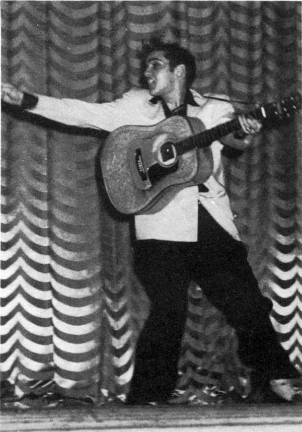 """Elvis onstage at the Carolina Theatre in Charlotte, NC - Feb. 10, 1956  Photo courtesy Brain Petersen  Twenty years old. Presley stands six feet, weighs 180 pounds. He has blue eyes, and brown hair which he wears rather long. He also wears a sleepy-eyed look when he walks on stage, because, as he told one interviewer, """"People expect me to look that way, so I do.""""Scotty Moore - The Carolina Theatre Charlotte, NC"""