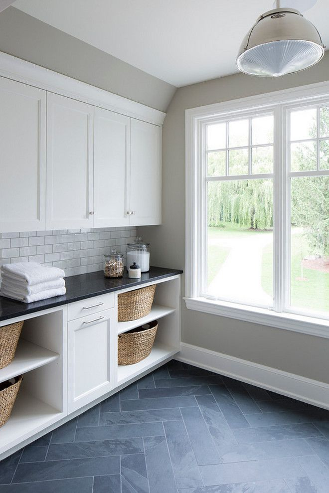 Laundry room. Herringbone tile slate. White cabinetry.