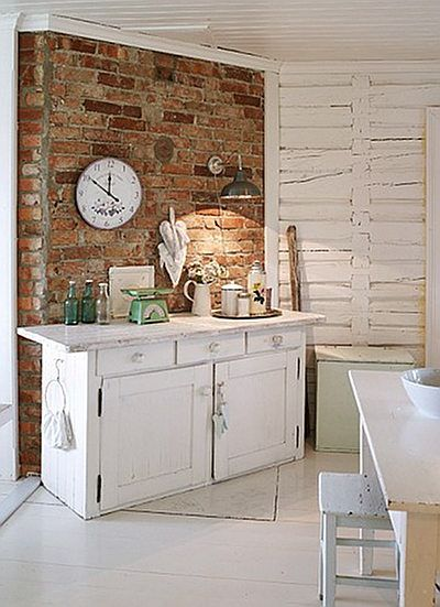 White cupboard against a brick wall. <3