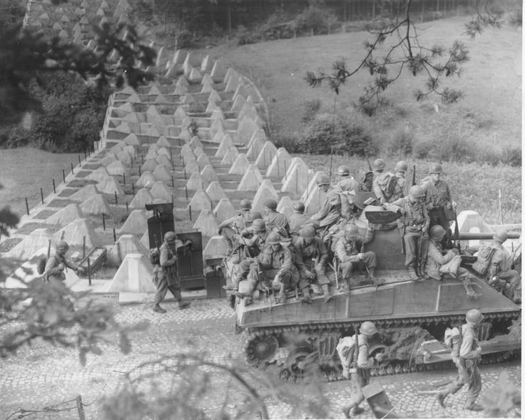 """US troops riding on the back of M4A2 Sherman tank and on foot cross the Siegfried Line into """"old"""" Germany as the Anglo-American all-front attack in 1944 develops."""