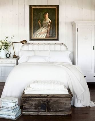 vintage and antique inspired bedroom with dark furniture white linens and a portrait that grabs the eye
